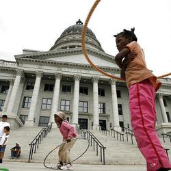 6-year-old Mainun Shale, center, and Fatuma Hussein, right, participate in a Hula Hoop contest during Capitol Discovery Day in Salt Lake City Saturday.