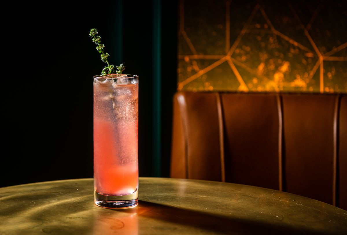 A tall glass  with a green stem garnish contains the grapefruit-pink Patio spritz, a blend of gin with orange-thyme shrub, apertif, and cava