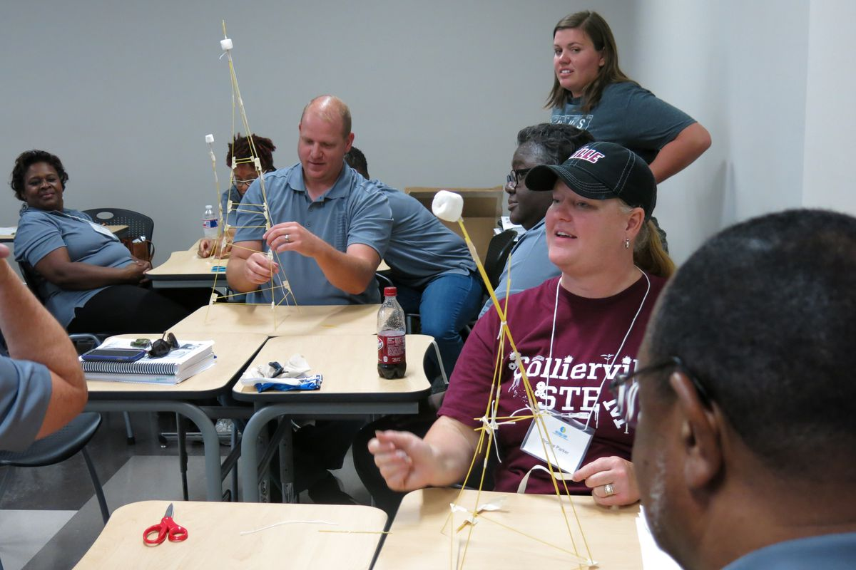 Collierville High School biology teacher Brooke Parker (center) constructs a tower using spaghetti strings during an ASM Materials Camp at Southwest Tennessee Community College in Memphis.