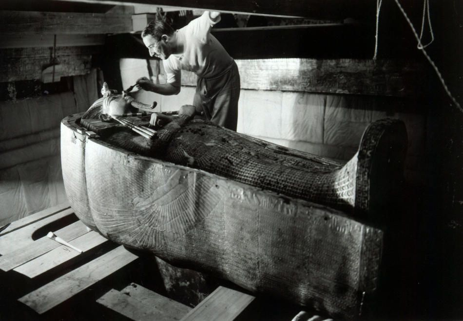 Howard Carter, the man who discovered Tutankhamen, examines his sarcophagus.