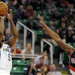 Utah Jazz point guard John Lucas III (5) shoots past the outstretched arm of Portland Trail Blazers point guard Damian Lillard (0) in the second half of a game at the Energy Solutions Arena on Wednesday, October 16, 2013.