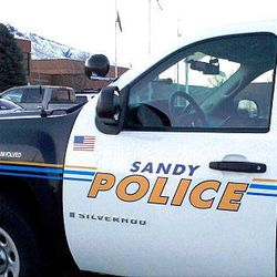 Sandy police vehicles sit outside Alta High School, where the principal and vice principal have been placed on leave.