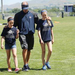 Utah State University football coach Matt Wells walks with his daughters Ella and Jadyn during a kids football camp in Logan Friday, June 12, 2015.