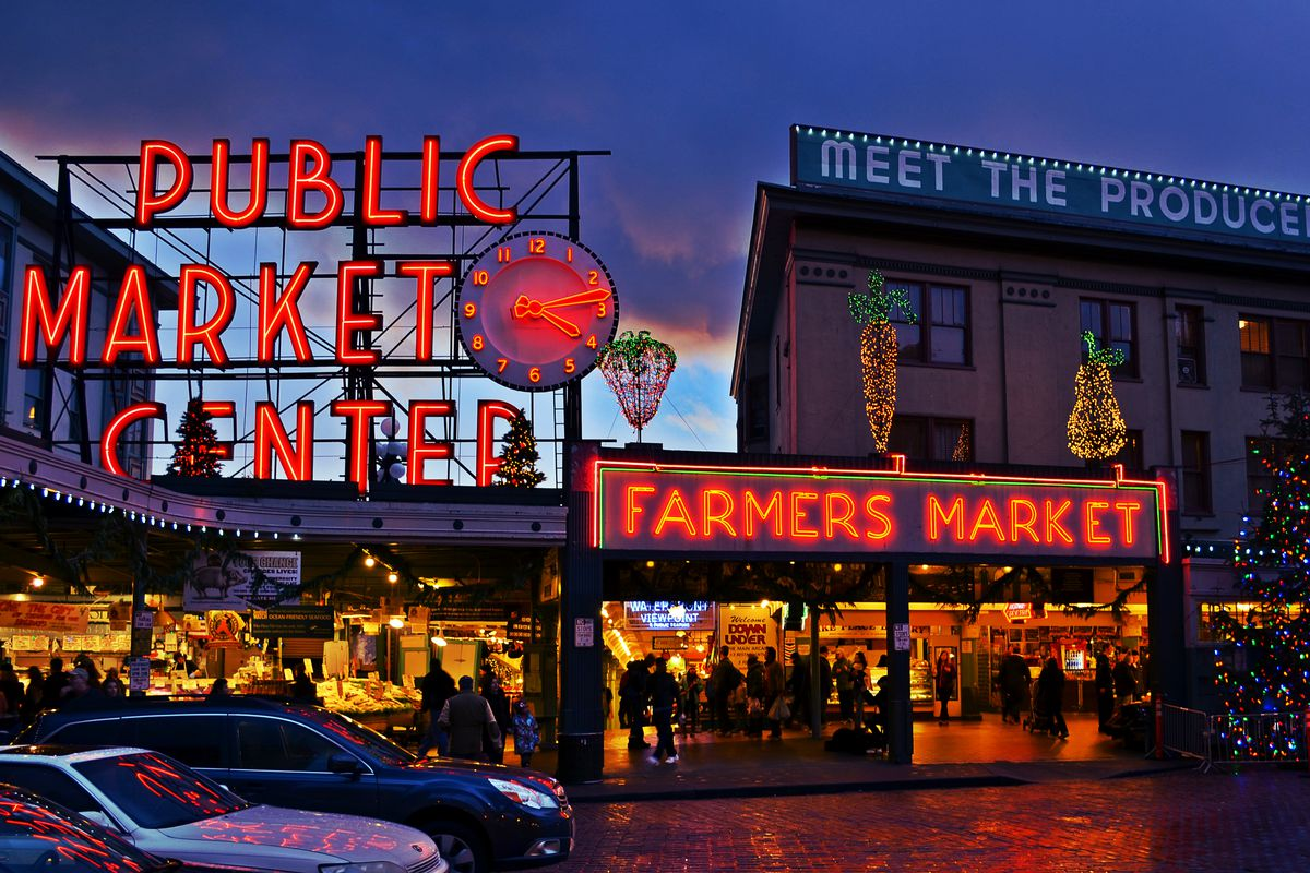 A view of Pike Place Market at night, with the iconic sign in red neon.