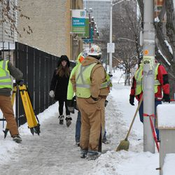 Surveying team having to dig out snow before setting up in position at Waveland & Kenmore