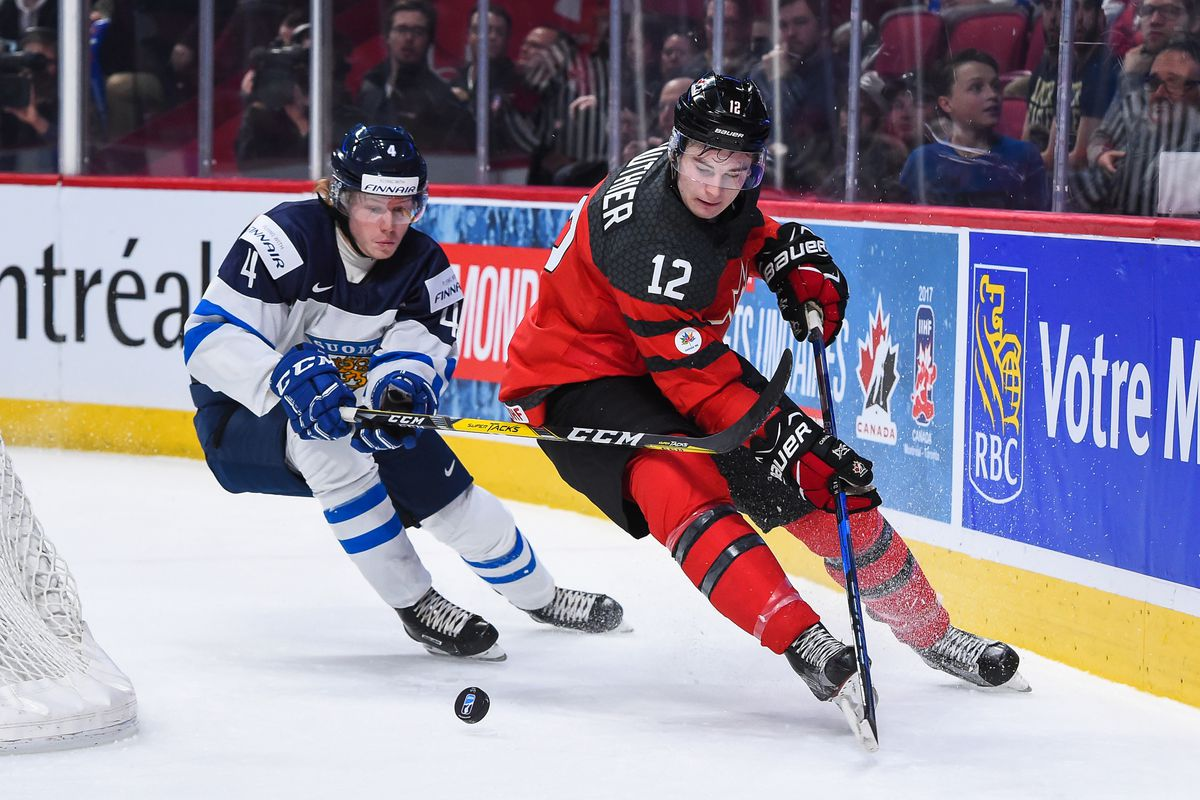 MONTREAL, QC - DECEMBER 19: Julien Gauthier #12 of Team Canada skates the puck against Robin Salo of Team Finland #4 during the IIHF exhibition game at the Bell Centre on December 19, 2016 in Montreal, Quebec, Canada.