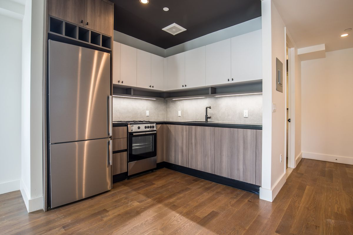 A small open kitchen with hardwood floors and white cabinetry.