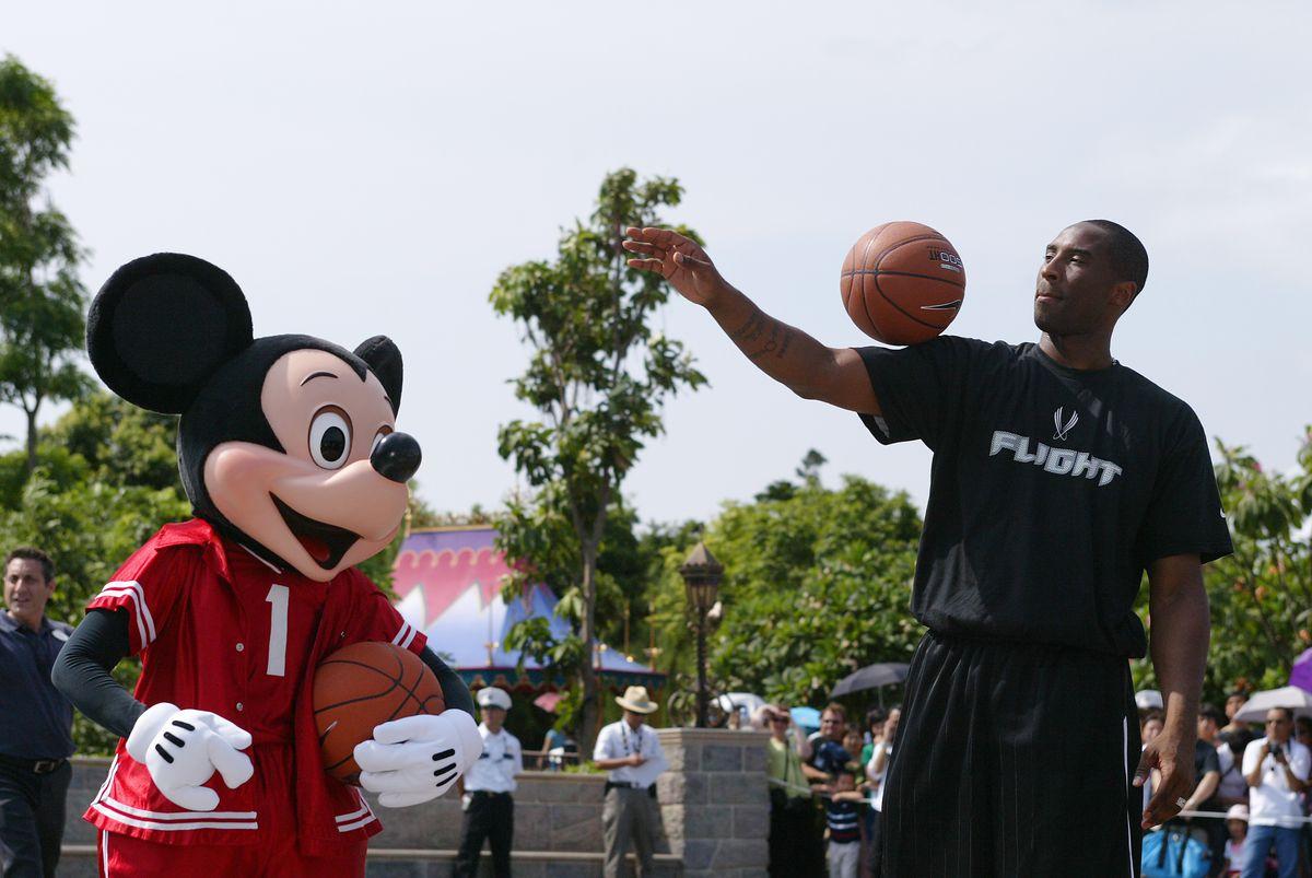 NBA basketball star Kobe Bryant (in black) dunk hoops in front of Disneyland Castle at Hong Kong Disneyland. 05 September 2006