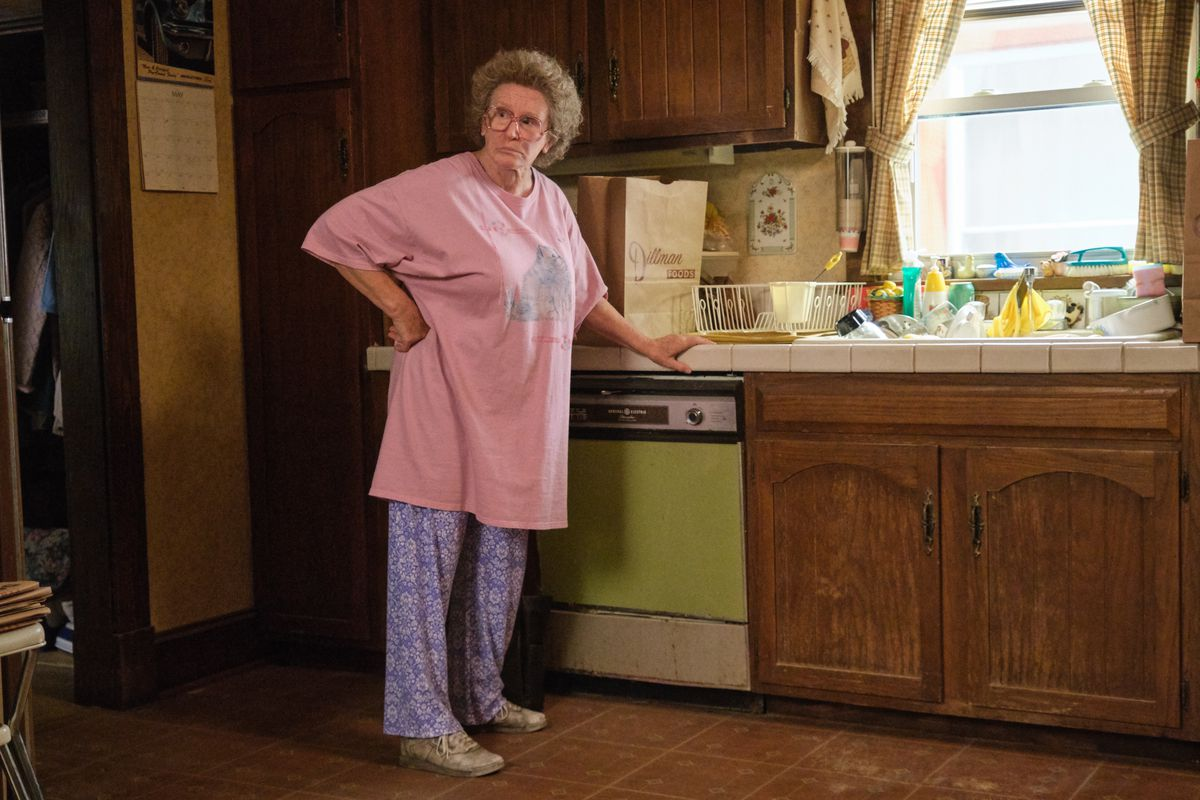 An elderly woman stands in a messy kitchen.