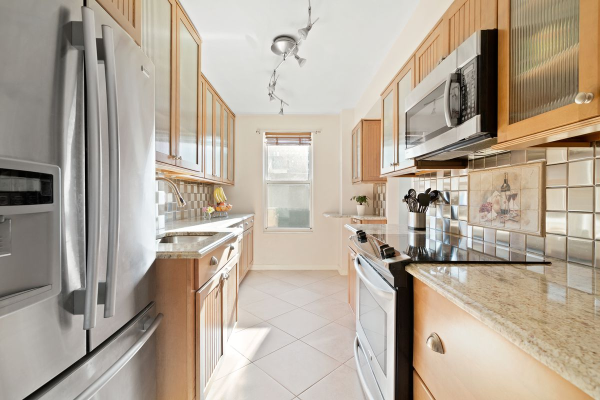 A kitchen with wood cabinetry and beige floor tiles.