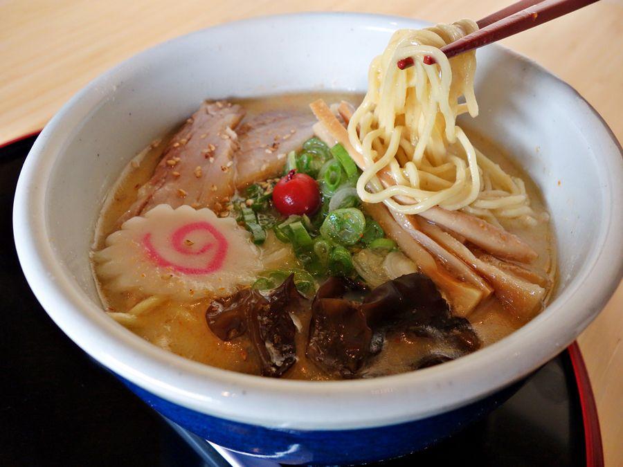 A white bowl with tonoktsu shio ramen and chopsticks lifting noodles.