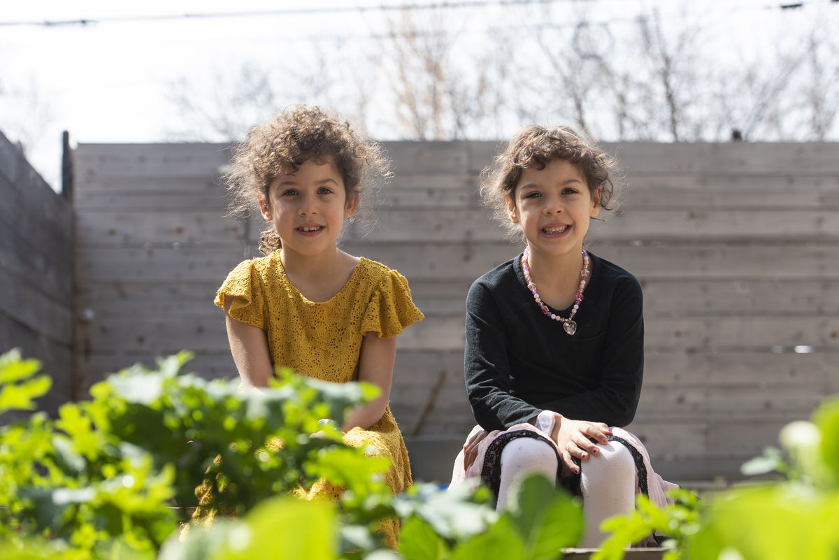 Hilde (left) and Elsie Shapiro-Braddy, 6 year old twins, sit in their garden where they've been spending their time during the coronavirus pandemic, Tuesday, April 28, 2020.