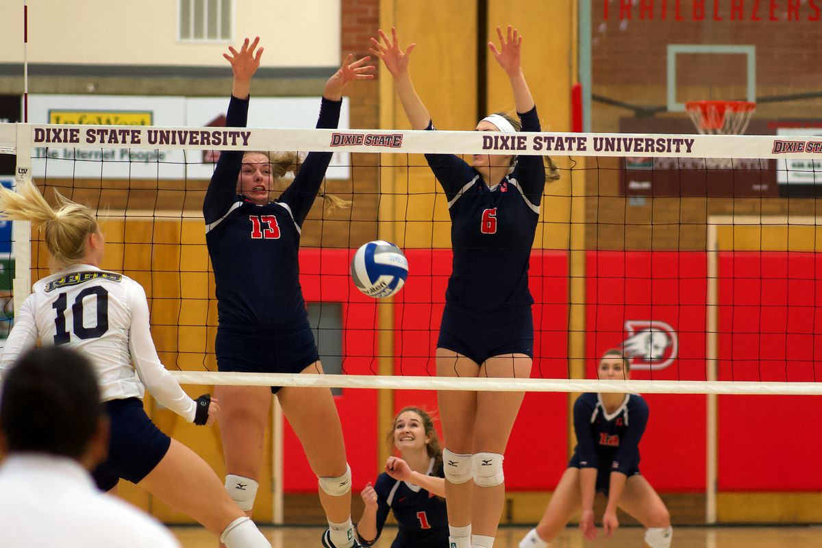 Dixie State's Megan Treanor (left-center) and Lauren Gammell (right-center) combine to block away the final Regis attack of the match to clinch the Trailblazers' sixth-straight win in a five-set thriller Saturday in St. George.