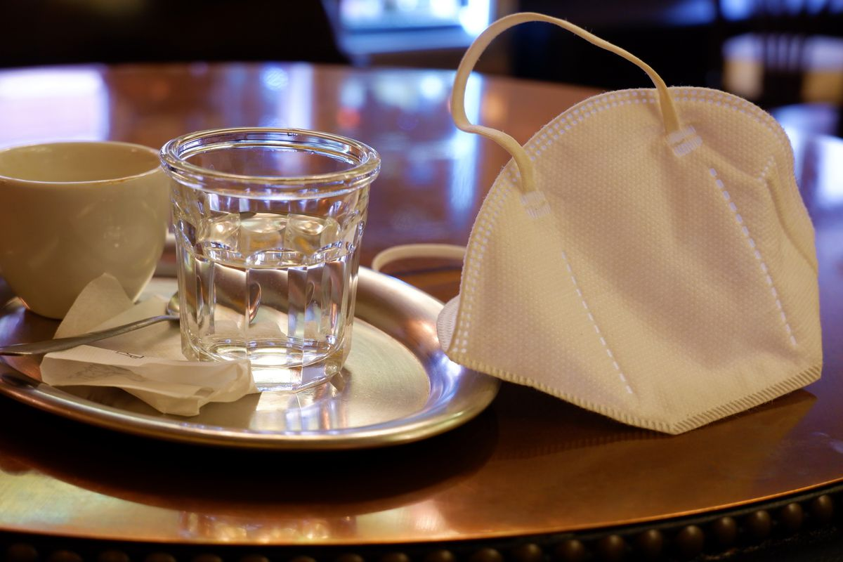 A cloth mask sits on a table next to an empty water glass and ceramic cup