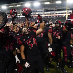 San Diego State players celebrate a 33-31 win in triple overtime against Utah in an NCAA college football game Saturday, Sept. 18, 2021, in Carson, Calif.