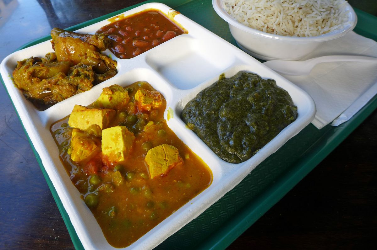 A white tray with four vegetarian dishes in shades of green and reddish brown with a bowl of rice on the side.