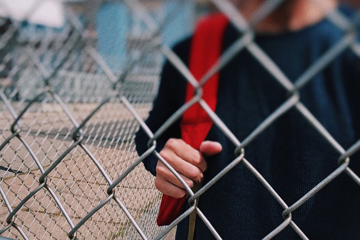 Close up of a student wearing a red backpack standing behind a wire fence.