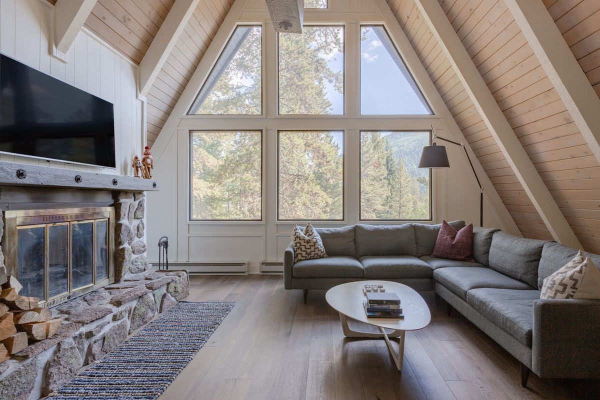 An interior photo of an A-frame with exposed wooden beams, a gray couch in the living room, a midcentury coffee table, and a large stone fireplace.