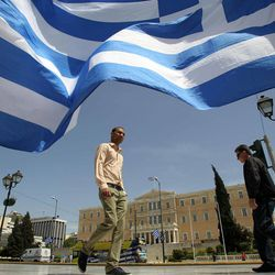 The Greek Parliament is seen behind country's flag in Athens, Friday, April 20, 2012. Polls indicate that Greece's majority Socialists are trailing their main conservative rivals by up to 7 percentage points nearly two weeks before crucial national elections. Voting is scheduled for Sunday, May 6.