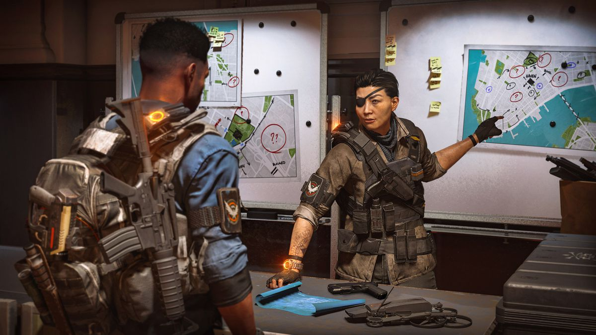 Faye Lau, a wounded Division commander wearing an eyepatch, instructs a Division agent by pointing at a map of lower Manhattan