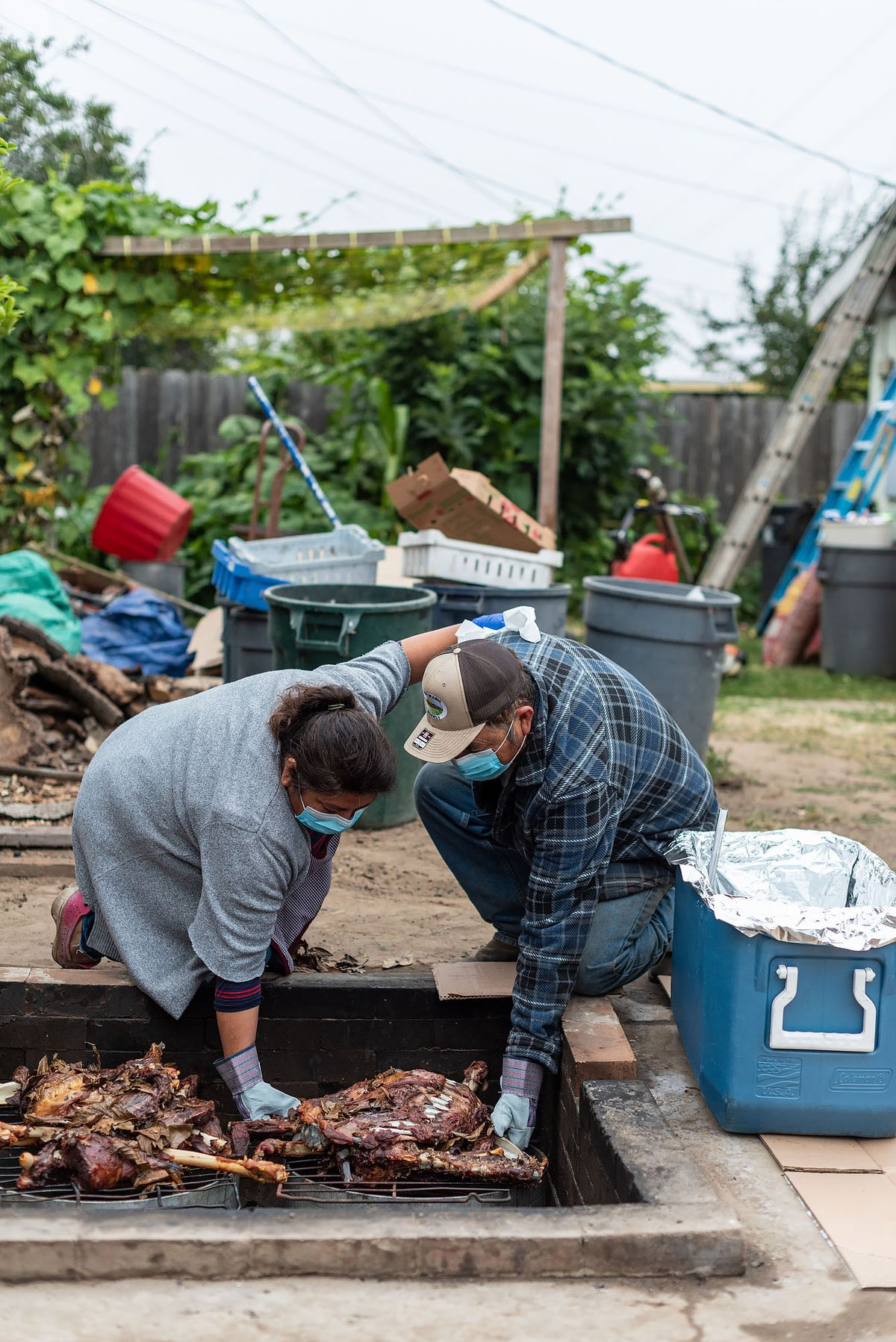 Candalaria and Francisco Bautista take their yique goat barbacoa out of a pit in their backyard.