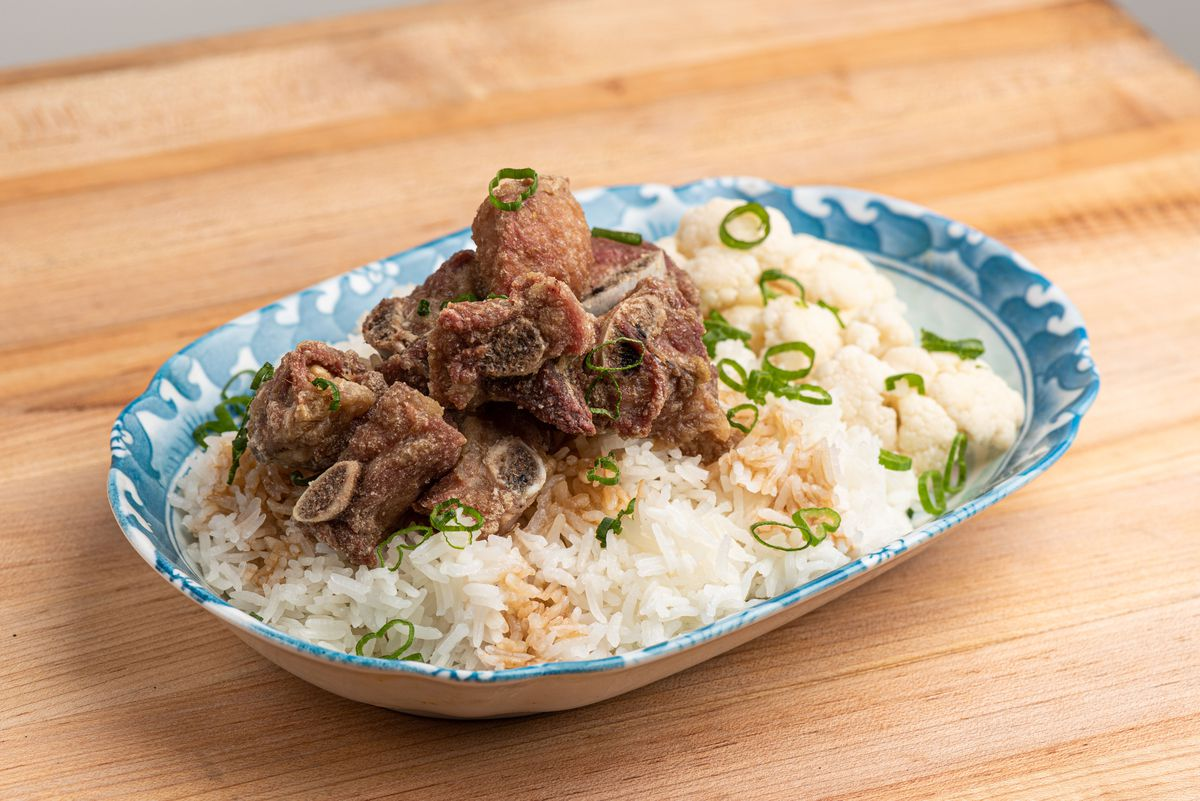 Fried pork riblets served over steamed white rice with green onion garnish.