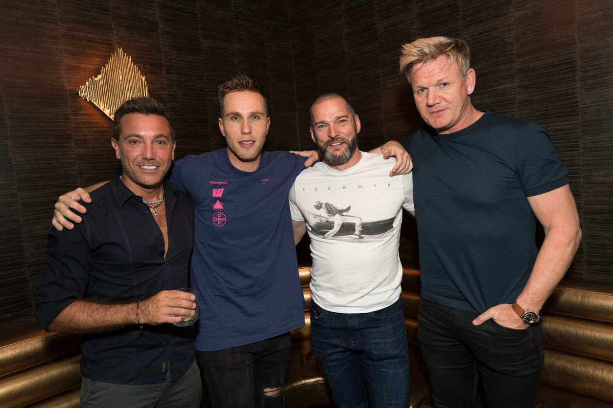 Four men pose for a photo