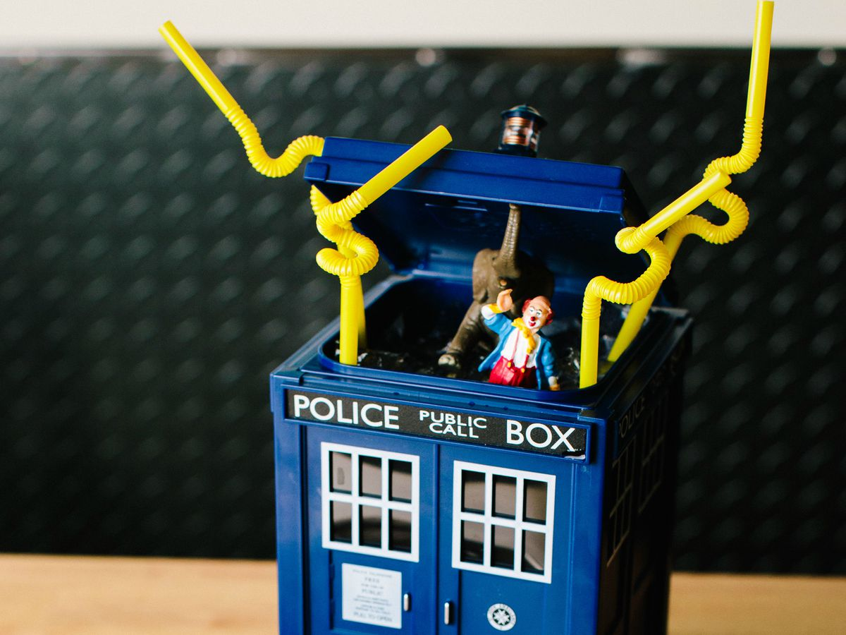 A Doctor Who-inspired Tardis drinking vessel with bendy straws and figurines coming out of it