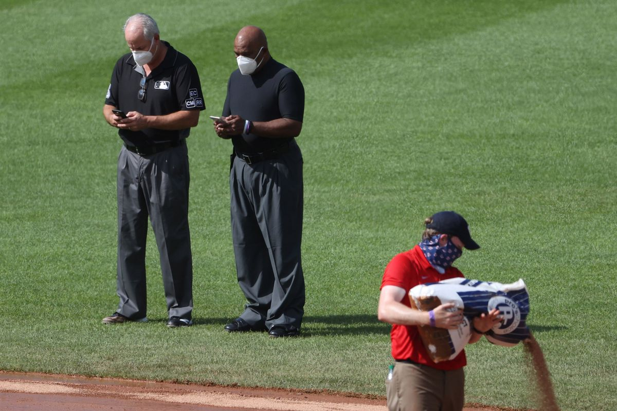 First base umpire Tim Timmons (M) and home plate umpire Laz Diaz (R) text on their phones as a member of the Washington Nationals grounds crew pours dirt onto the infield during a delay in the game between the Nationals and the Baltimore Orioles at Nationals Park.