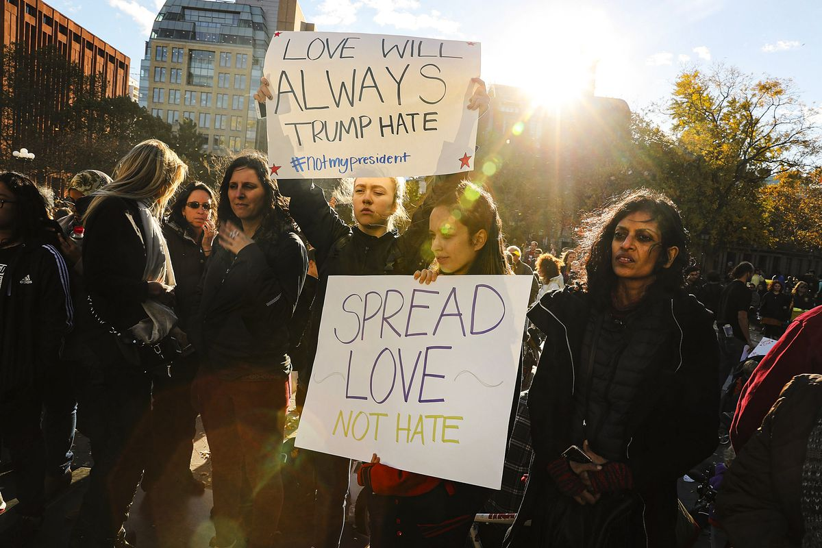 """A woman holds a sign that reads, """"Spread love, not hate,"""" while another holds a sign over her head that reads, """"Love will always trump hate."""""""