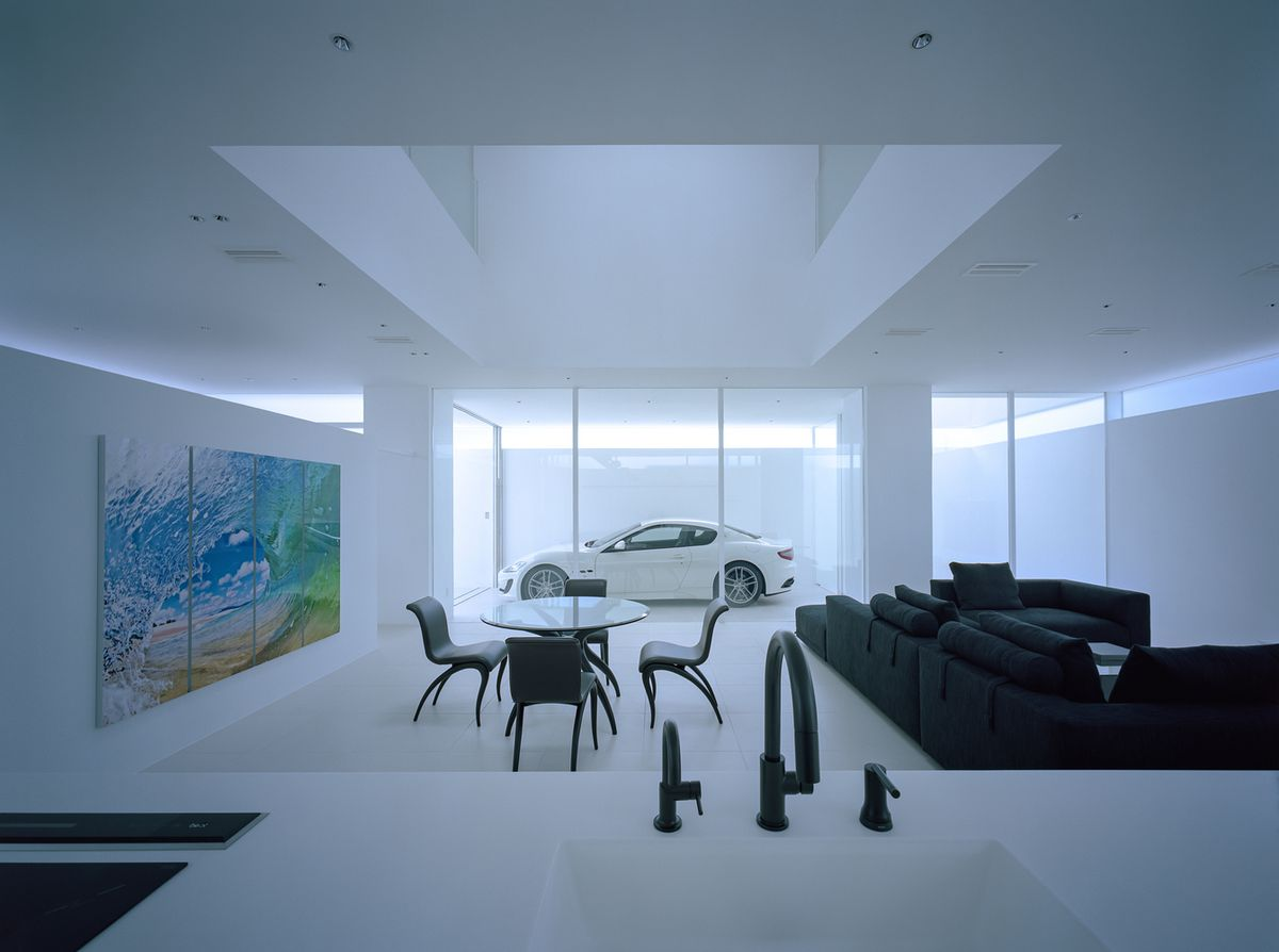 Modern living room with glass wall that looks onto garage.