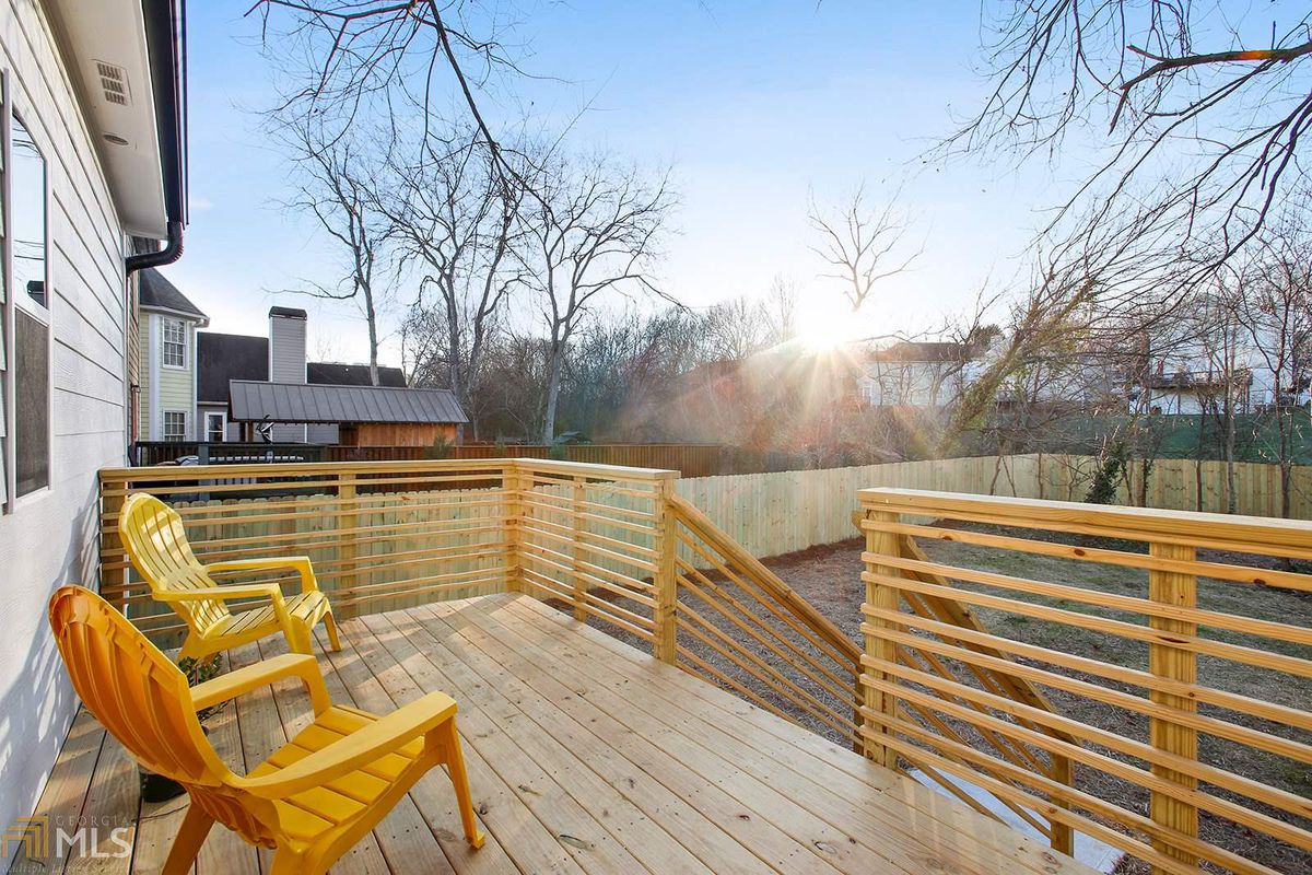 Deck with two chairs facing the backyard.