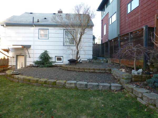 A backyard with some raised areas lined by rocks