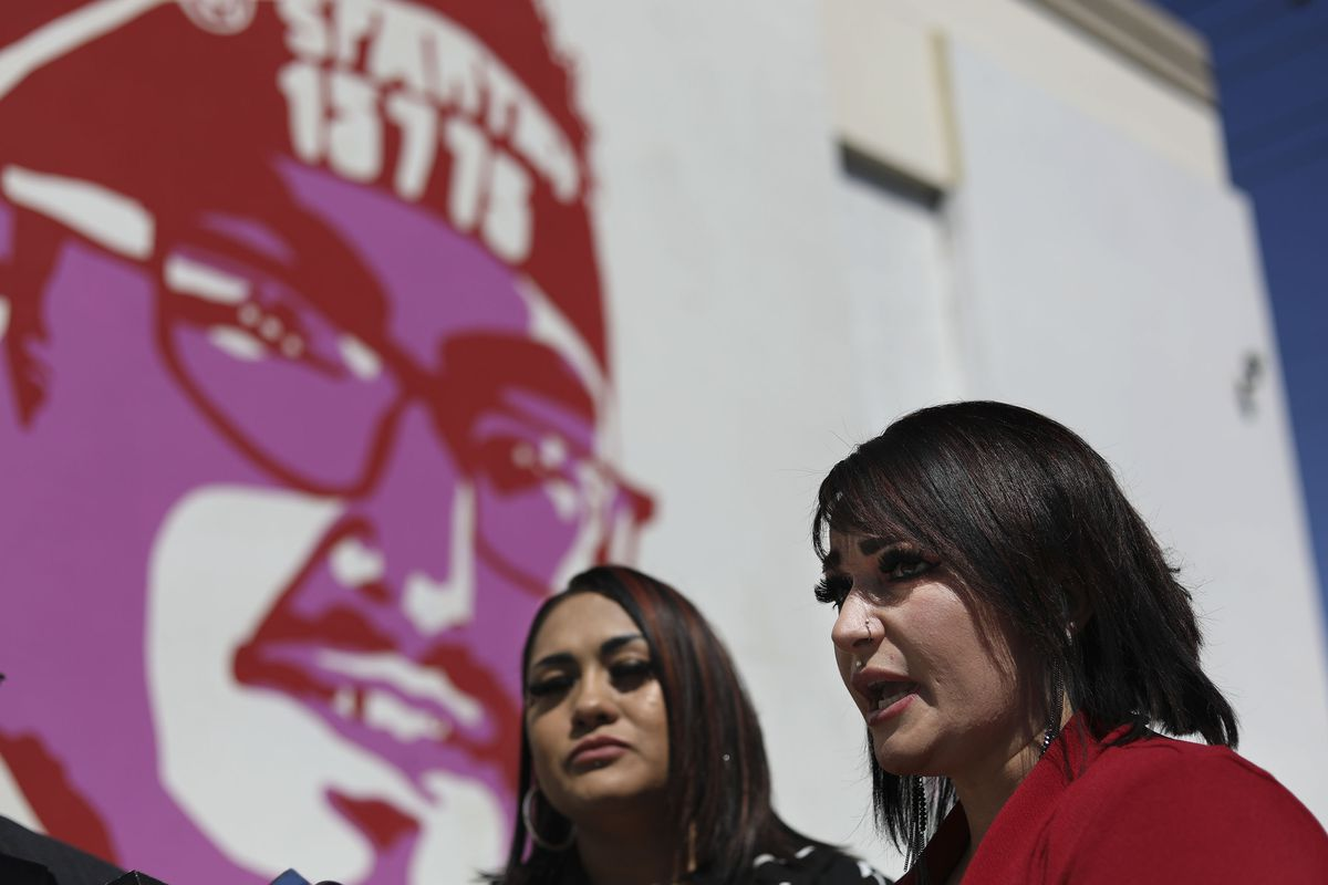 Anna Herrera, left, and Brittny Herrera, cousins of Bryan Peña Valencia, hold a press conference underneath Peña Valencia's portrait on a building at 900 South and 300 West in Salt Lake City on Wednesday, May 5, 2021. Peña Valencia was shot by a Unified police officer on March 21, 2020, after police responded to a 911 call about gunshots in the area of 6200 S. Bangerter Highway.