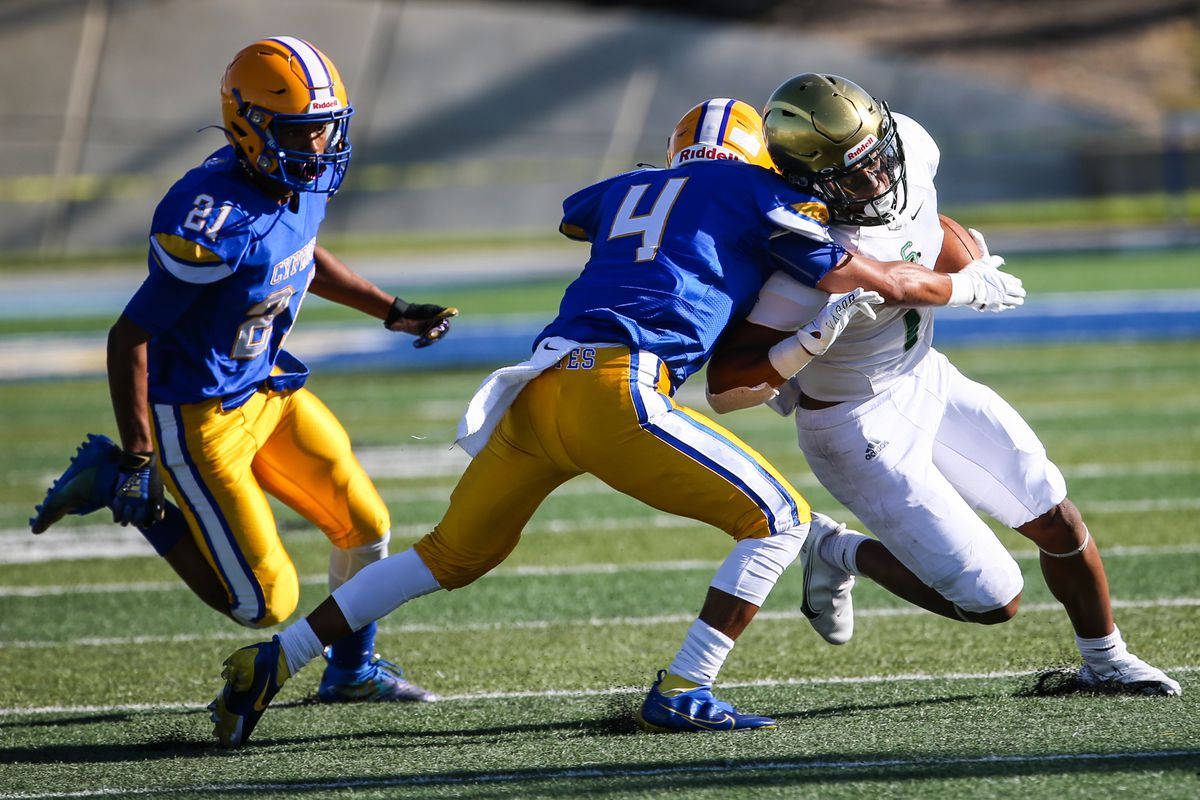Cyprus' Adrian Banuelos (4) attempts to stop Snow Canyon's Bretton Stone (1) with Cary Butler (21) following behind during a high school football game at Cyprus High School in Magna on Friday, Aug. 14, 2020.