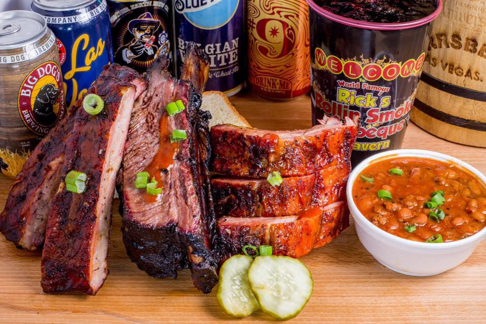 A stack of ribs with baked beans in a bowl