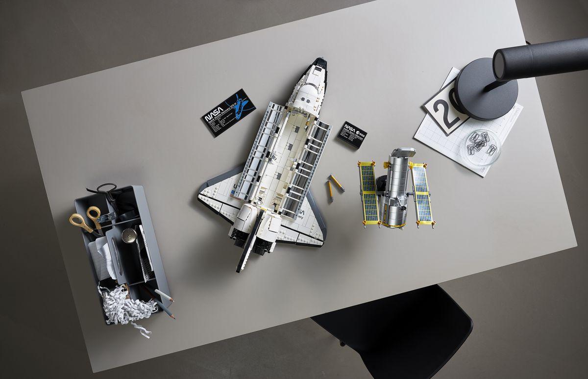 Una vista de pájaro del transbordador espacial Lego sobre una mesa, con la bahía de carga útil abierta para mostrar el interior brillante de sus puertas. El telescopio Hubble está al lado del transbordador.