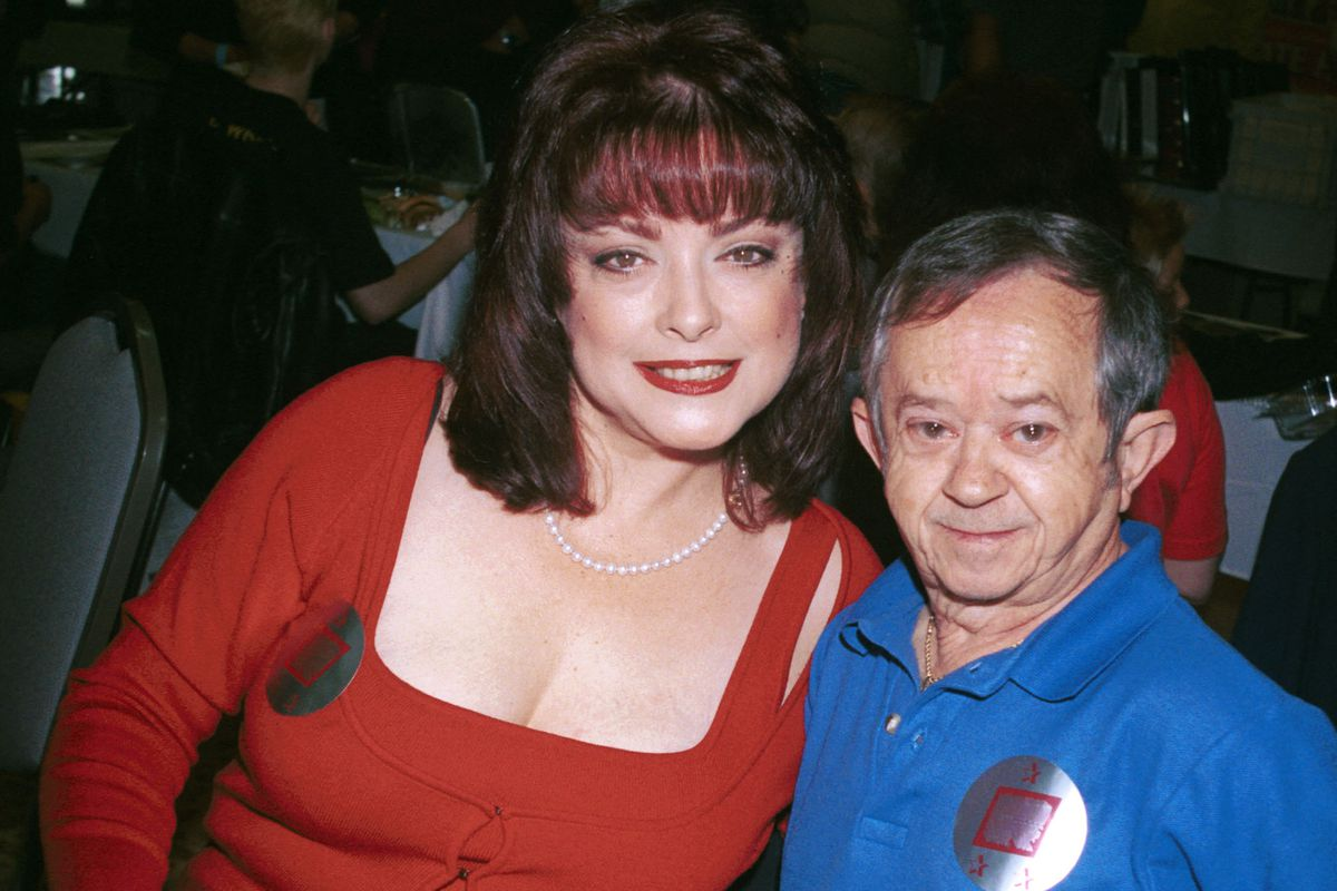 """Actors Lisa Loring (who starred as Wednesday) and Felix Silla (who starred as Cousin Itt) from the mid-60's television series """"The Addams Family"""" attend the """"Hollywood Collectors and Celebrities Show"""" in 2001 in North Hollywood, California."""