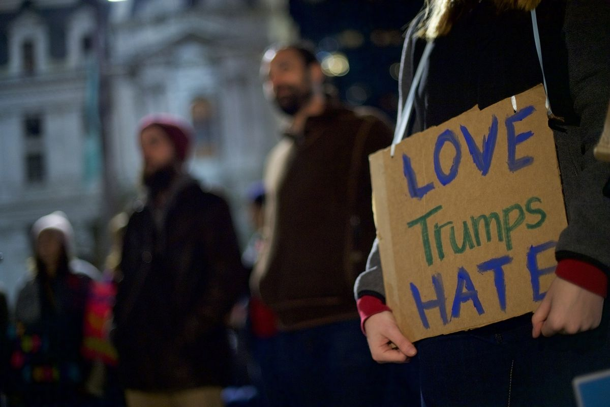 """An anti-Trump protester holds a """"love trumps hate"""" sign."""