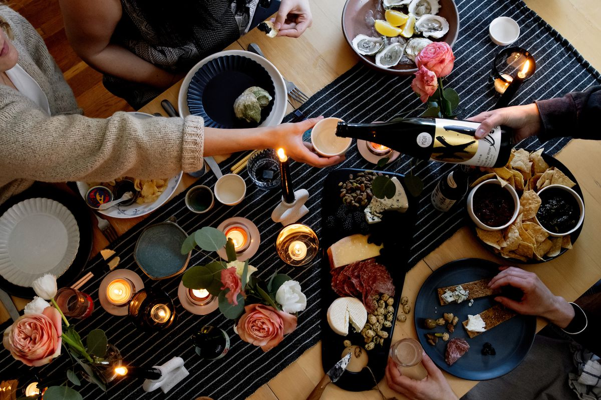 Overhead view of a spread of people pouring sake over a table. There are also oysters on the table.