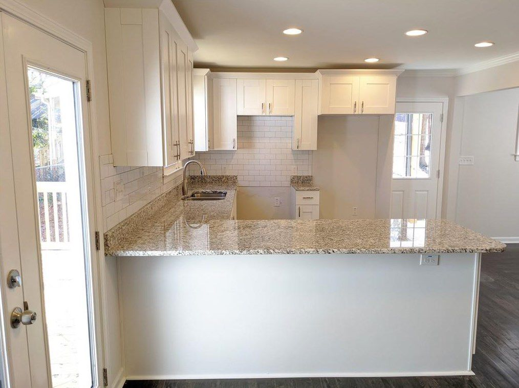 A large white kitchen with granite countertops and wood.