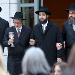 Rabbi Avraham Cohen, second from left, and Rabbi Benny Zippel, right, escort Rabbi Mendy Cohen, the groom, during his traditional Chabad Lubavitch Jewish wedding at the Grand America Hotel in Salt Lake City on Monday, Sept. 12, 2016. On the far left, is Rabbi Avremi Zippel, brother of the bride.