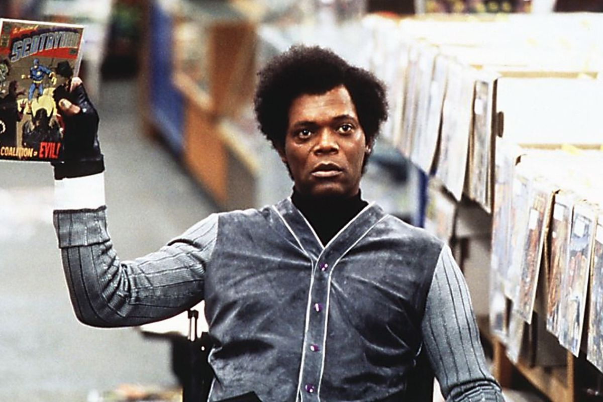Samuel L. Jackson, seated in a wheelchair, holds up a comic book