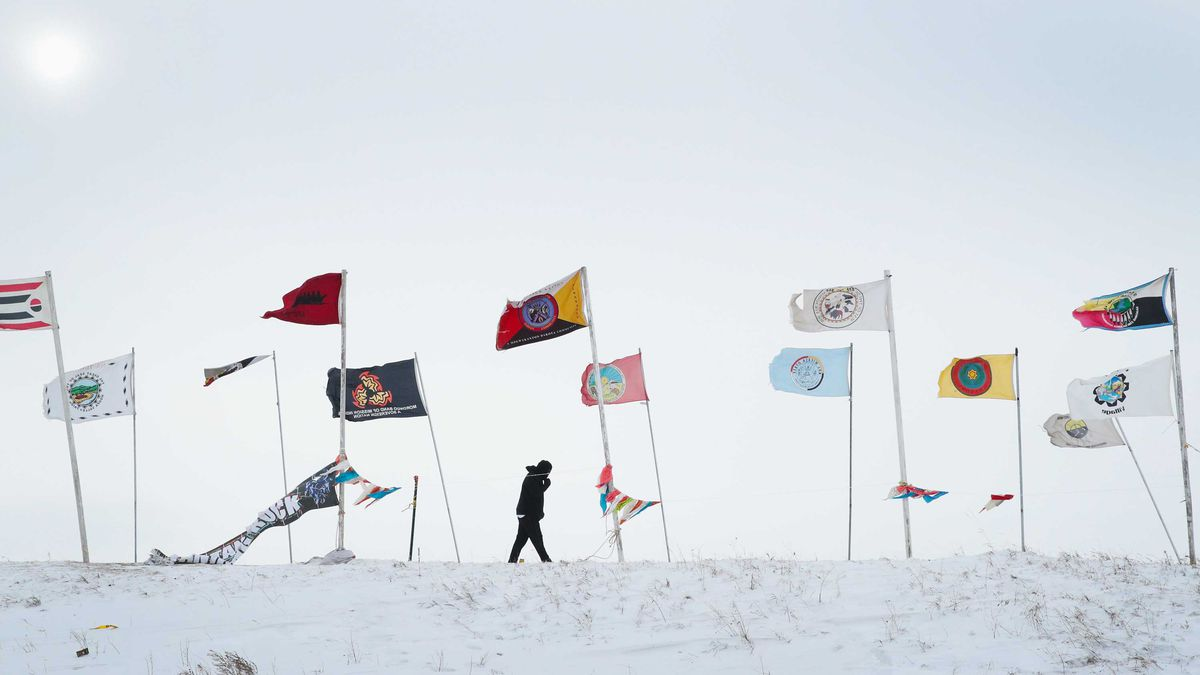 A figure on a windswept road walks past a series of flags.