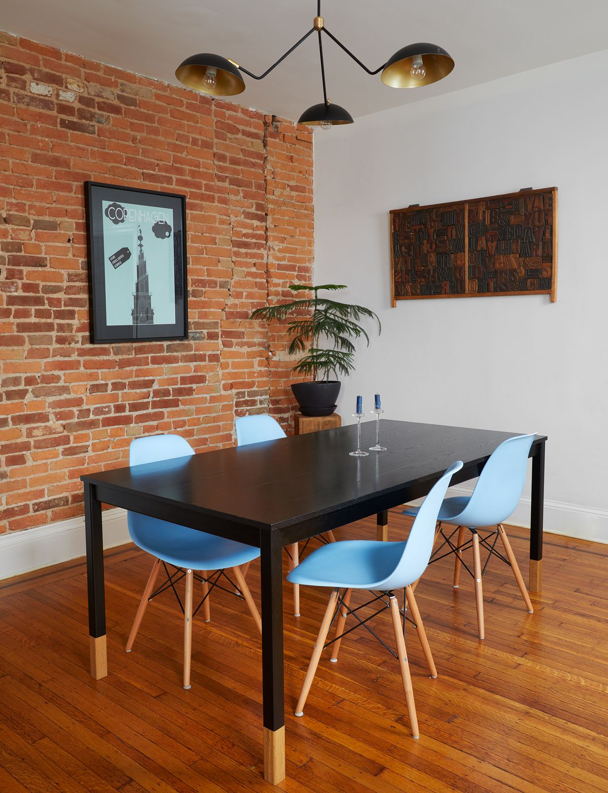 A dining room area. There is a large black table flanked by blue chairs. One of the walls is exposed red brick. The other wall is painted white. There is a plant in a planter in the corner. A work of art hangs on one wall. There is a hanging light fixture