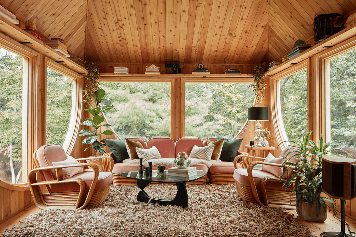 Living room surrounded by semi-circle windows, and a brown rug.
