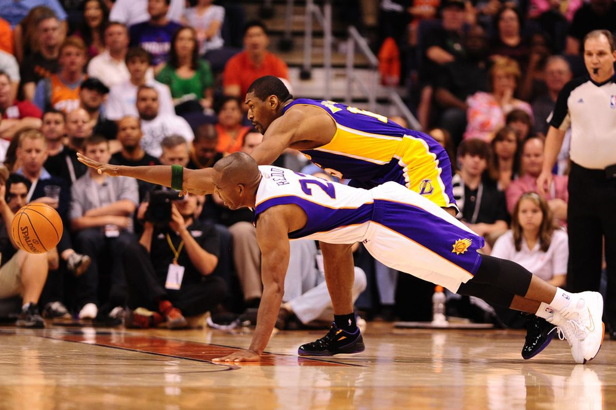 Apr. 7, 2012; Phoenix, AZ, USA; Los Angeles Lakers forward (15) Metta World Peace and Phoenix Suns guard (22) Michael Redd dive for a loose ball in the first half at the US Airways Center. Mandatory Credit: Mark J. Rebilas-US PRESSWIRE