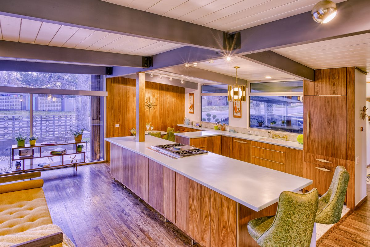The interior of a midcentury modern home. There is a kitchen island, chairs, wooden cabinetry, and a table. There are floor to ceiling windows.
