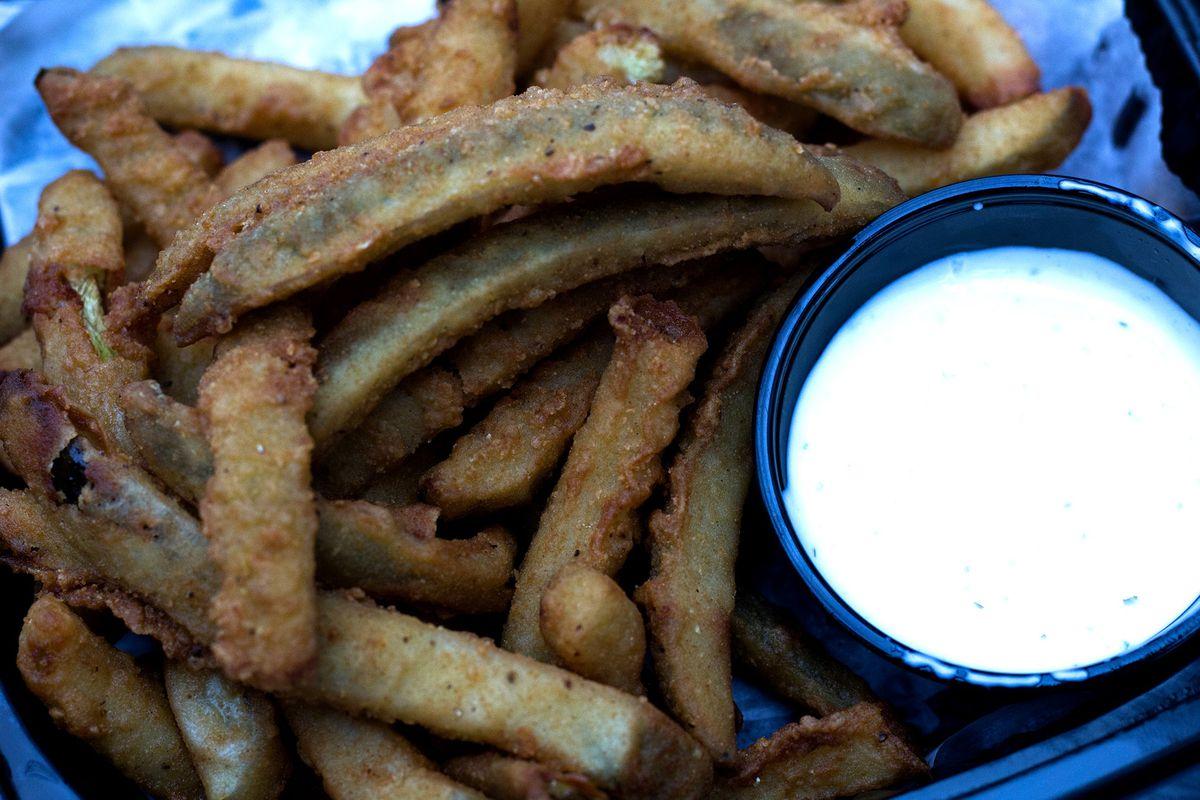 A plate of fried pickle spears, accompanied by a ramekin of ranch dressing