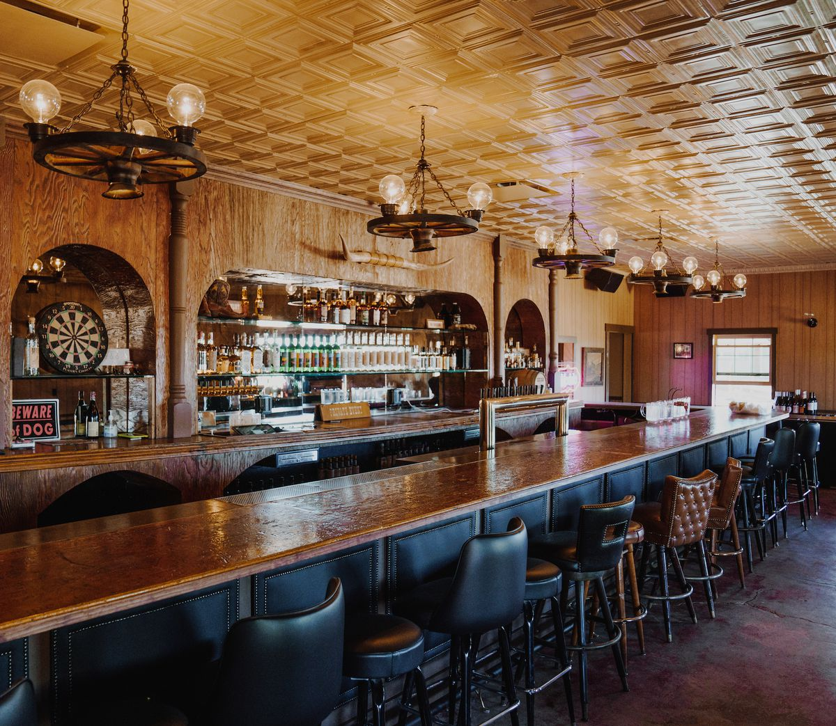 The dimly lit interior of a Western bar with leather stools.